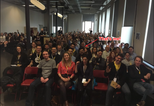An image taken from the main stage of the Game UX Summit, showing a full room of UX professionals waving at the camera.